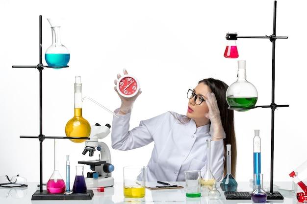 Vooraanzicht vrouwelijke chemicus in wit medisch pak met klokken op witte achtergrond wetenschap virus lab covid pandemie