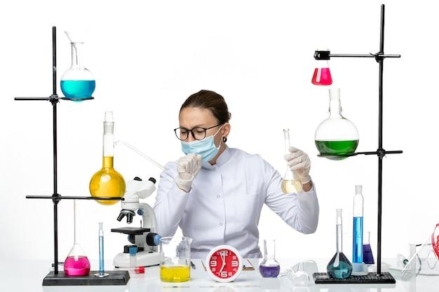 Vooraanzicht vrouwelijke chemicus in wit medisch pak met masker houden oplossing hoesten op witte achtergrond scheikundige lab virus covid-splash