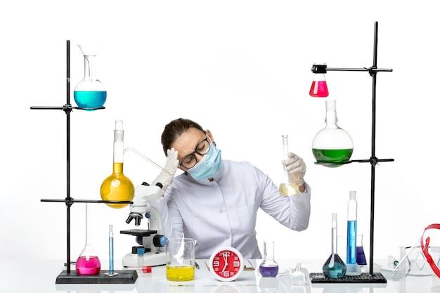 Vooraanzicht vrouwelijke chemicus in wit medisch pak met masker houden oplossing met hoofdpijn op witte achtergrond chemicus lab virus covid splash