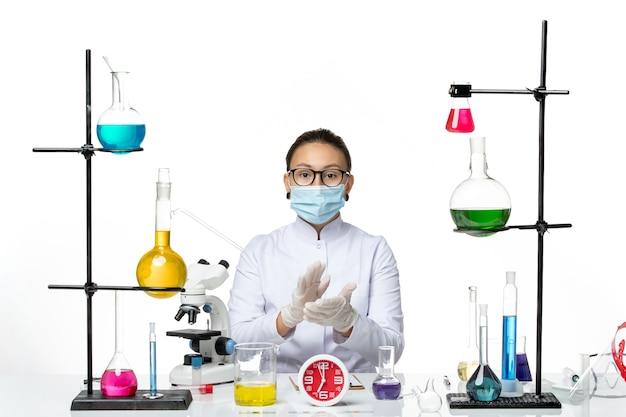 Vooraanzicht vrouwelijke chemicus in wit medisch pak met masker klappen op witte achtergrond chemicus virus covid-splash lab