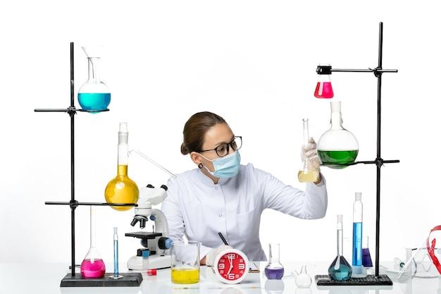 Vooraanzicht vrouwelijke chemicus in wit medisch pak met masker schrijven van notities op witte achtergrond scheikundige lab virus covid splash