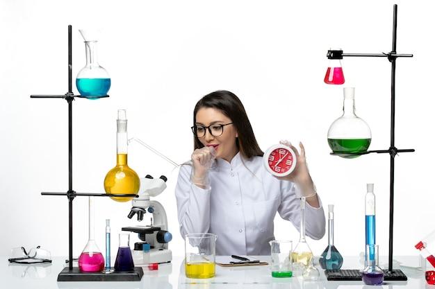 Vooraanzicht vrouwelijke chemicus in wit medisch pak met rode klokken en hoesten op witte achtergrond science virus lab covid-pandemie
