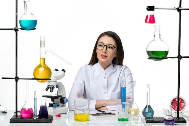 Vooraanzicht vrouwelijke chemicus in wit medisch pak werken en notities schrijven op de lichte witte achtergrond science virus covid- pandemic lab