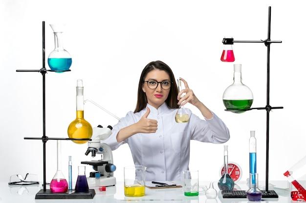 Vooraanzicht vrouwelijke chemicus in wit medisch pak werken met oplossingen op witte achtergrond covid science pandemic lab virus