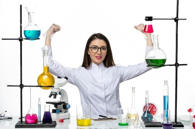 Vooraanzicht vrouwelijke chemicus in wit medisch pak zittend met verschillende oplossingen buigen op witte achtergrond science virus covid pandemic lab