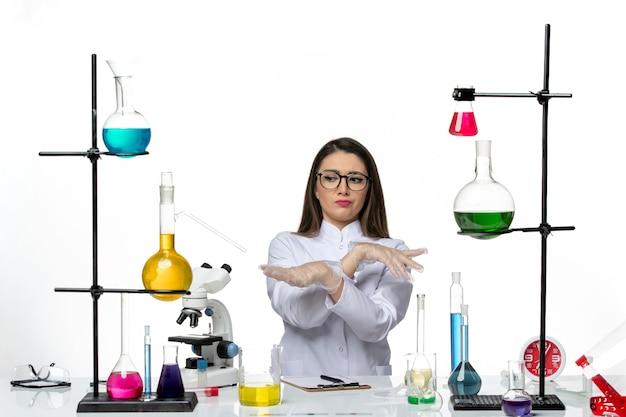Vooraanzicht vrouwelijke chemicus in wit medisch pak zittend op lichte witte achtergrond lab virus covid pandemie wetenschap