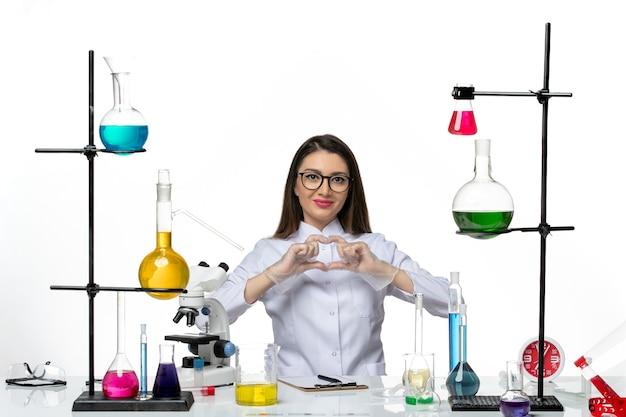 Vooraanzicht vrouwelijke chemicus in witte medische pak zitten en glimlachend op witte achtergrond lab wetenschap virus covid pandemie