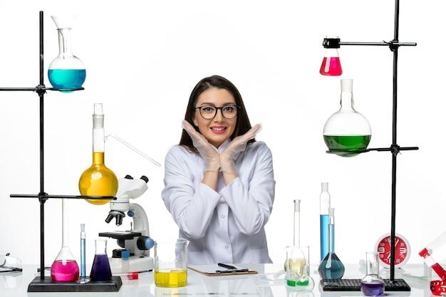 Vooraanzicht vrouwelijke chemicus in witte medische pak zitten en poseren glimlachend op witte achtergrond lab wetenschap virus covid pandemie