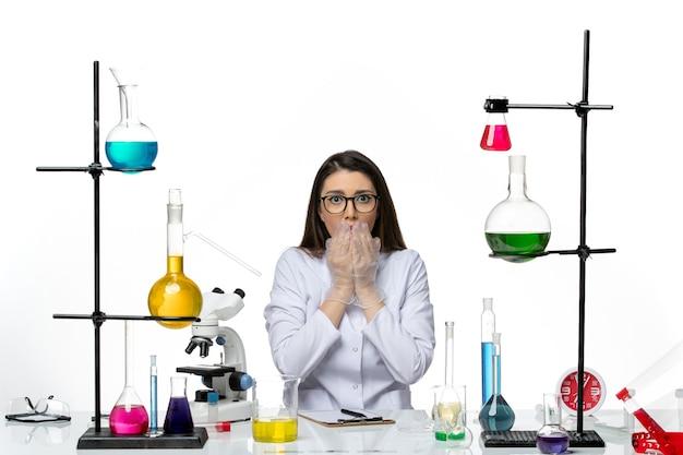 Vooraanzicht vrouwelijke chemicus in witte medische pak zitten en poseren op witte achtergrond lab wetenschap virus covid pandemie