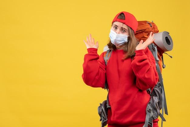 Vooraanzicht vrouwelijke kampeerder met rugzak en masker staande op gele muur