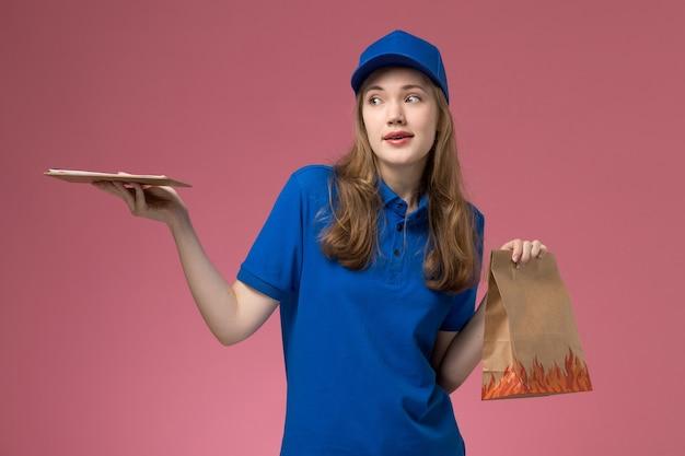 Vooraanzicht vrouwelijke koerier in blauw uniform bedrijf blocnote en voedselpakket op lichtroze achtergrond baan werknemer dienst uniform bedrijf