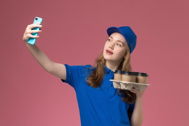 Vooraanzicht vrouwelijke koerier in blauw uniform die een selfie met bezorging koffiekopjes neemt op roze-licht bureau dienst uniform bedrijf baan