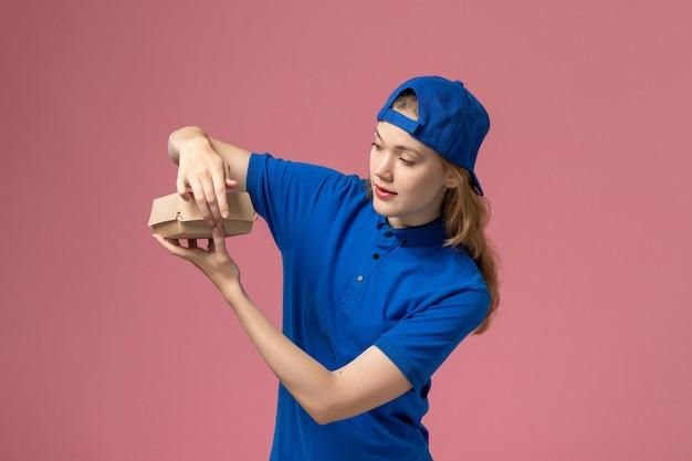 Vooraanzicht vrouwelijke koerier in blauw uniform en cape die een klein voedselpakket voor bezorging vasthoudt en het op de roze muur opent, bezorgdienst uniform