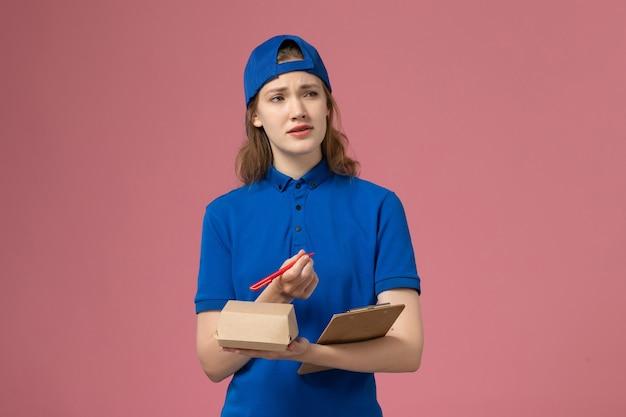 Vooraanzicht vrouwelijke koerier in blauw uniform en cape die kleine notitieblok voor bezorgvoedselpakket vasthoudt en op de roze muur schrijft, bezorgdienstmedewerker werk
