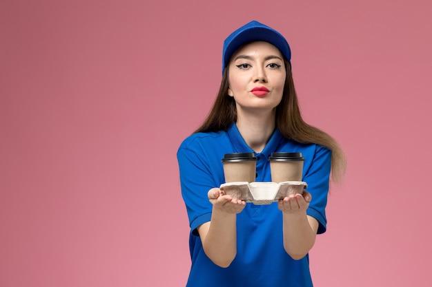 Vooraanzicht vrouwelijke koerier in blauw uniform en cape die koffiekopjes levert op de roze muurbaan