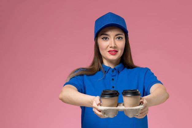 Vooraanzicht vrouwelijke koerier in blauw uniform en cape die koffiekopjes op roze muur levert