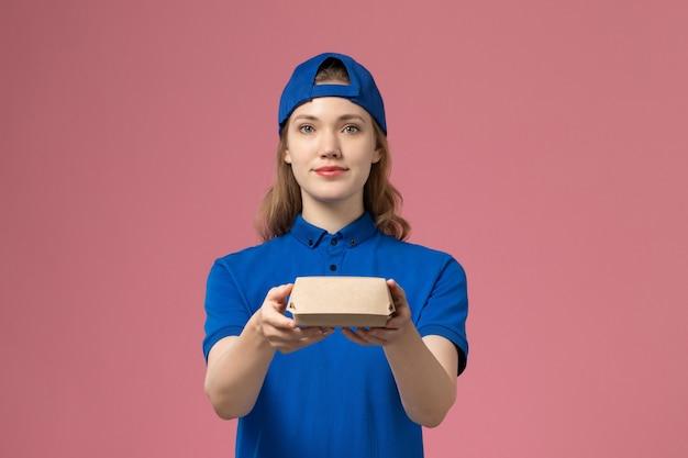 Vooraanzicht vrouwelijke koerier in blauw uniform en cape die weinig bezorgingsvoedselpakket op de roze achtergrond houden levering uniform dienst bedrijf werk werknemer meisje baan