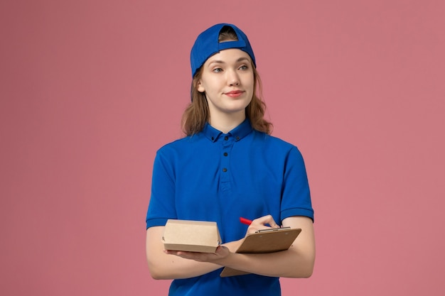 Vooraanzicht vrouwelijke koerier in blauw uniform en cape die weinig voedselpakket en blocnote houdt die op roze muur schrijft, medewerker van de bezorgdienst