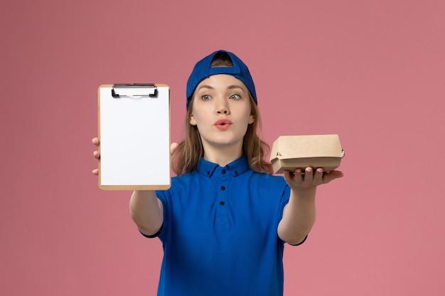 Vooraanzicht vrouwelijke koerier in blauw uniform en cape die weinig voedselpakket en blocnote op de roze medewerker van de bureauleveringsdienst houdt
