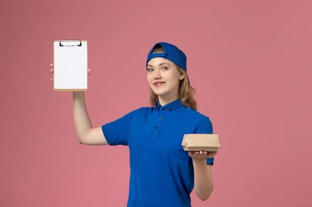 Vooraanzicht vrouwelijke koerier in blauw uniform en cape die weinig voedselpakket en blocnote op roze muur, baan van de bezorgdienstmedewerker houdt