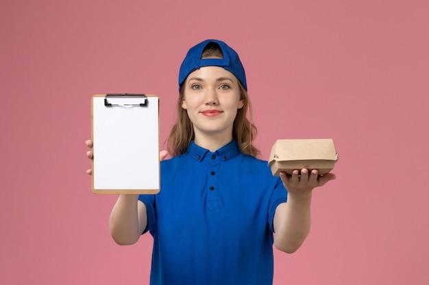 Vooraanzicht vrouwelijke koerier in blauw uniform en cape die weinig voedselpakket en blocnote op roze muur, bezorgdienstmedewerker houdt