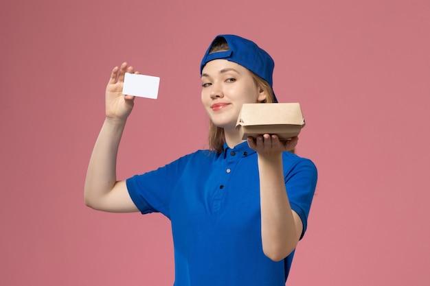 Vooraanzicht vrouwelijke koerier in blauw uniform en cape die weinig voedselpakket met kaartje op de roze muur houdt, werknemer bezorgdienst