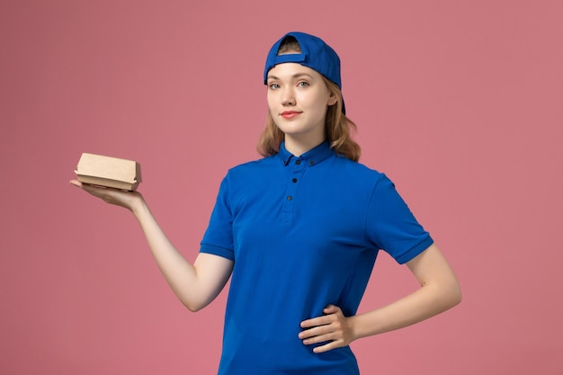 Vooraanzicht vrouwelijke koerier in blauw uniform en cape die weinig voedselpakket van de levering op roze achtergrond het bedrijf van de de dienstarbeider van de baanlevering houdt