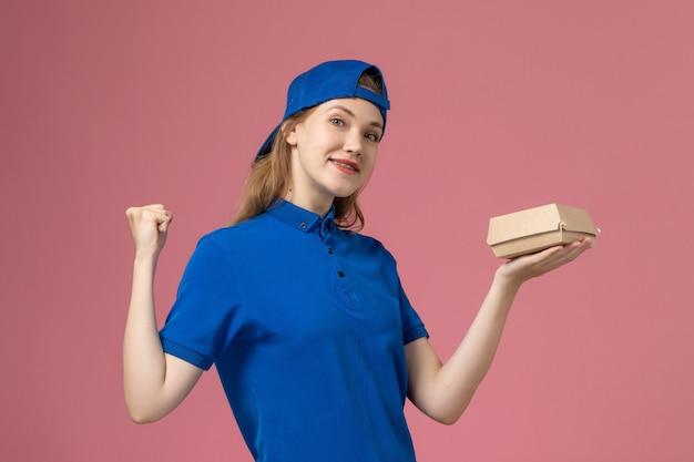 Vooraanzicht vrouwelijke koerier in blauw uniform en cape die weinig voedselpakket voor bezorging houdt en zich verheugt op roze muur, meisje van de dienstbezorging uniform