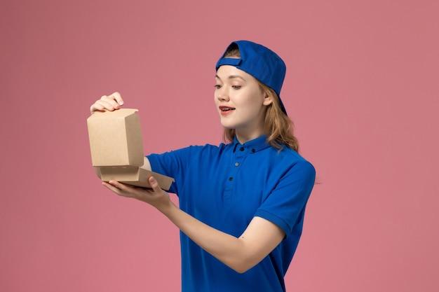 Vooraanzicht vrouwelijke koerier in blauw uniform en cape die weinig voedselpakket voor bezorging op lichtroze muur houdt, baan voor bezorgingsuniform