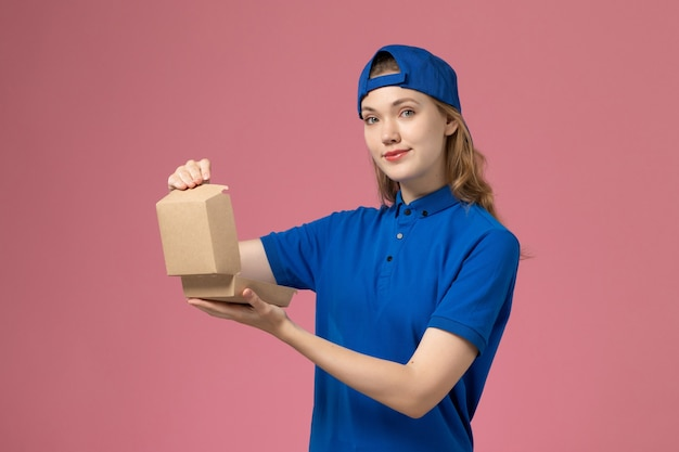 Vooraanzicht vrouwelijke koerier in blauw uniform en cape die weinig voedselpakket voor bezorging op lichtroze muur houdt, medewerker van de bezorgdienst