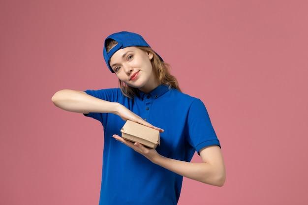 Vooraanzicht vrouwelijke koerier in blauw uniform en cape die weinig voedselpakket voor bezorging op lichtroze muur, uniforme servicemedewerker van de bezorgbaan houdt