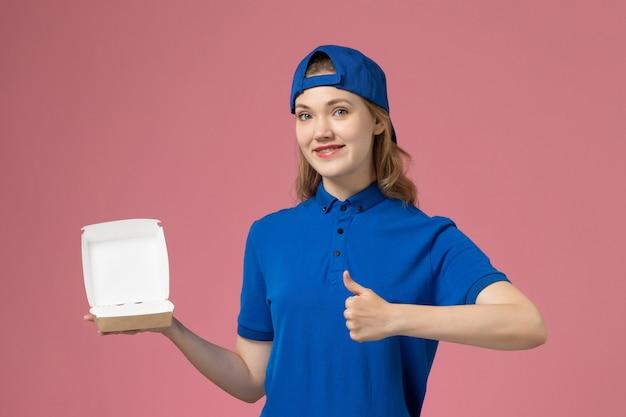 Vooraanzicht vrouwelijke koerier in blauw uniform en cape die weinig voedselpakket voor bezorging op roze muur houdt, werknemer van de baan van de dienst van de levering uniforme dienst