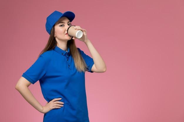 Vooraanzicht vrouwelijke koerier in blauw uniform en cape koffie drinken op de roze muur baan