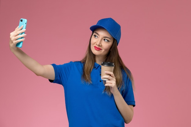 Vooraanzicht vrouwelijke koerier in blauw uniform en cape levering koffiekopje houden selfie op roze muur