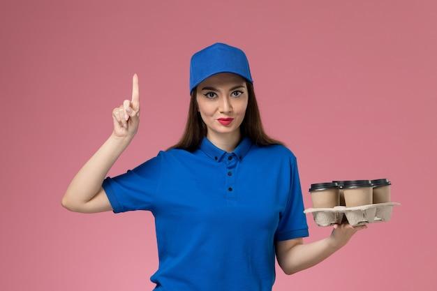 Vooraanzicht vrouwelijke koerier in blauw uniform en cape levering koffiekopjes met opgeheven vinger op roze muur te houden