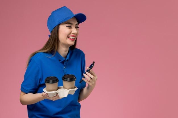 Vooraanzicht vrouwelijke koerier in blauw uniform en cape met bezorging koffiekopjes lachend op de roze muur