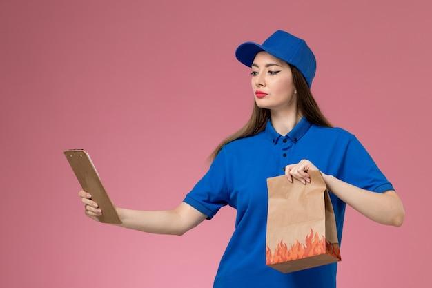 Vooraanzicht vrouwelijke koerier in blauw uniform en cape met blocnote papier voedselpakket op de roze muur