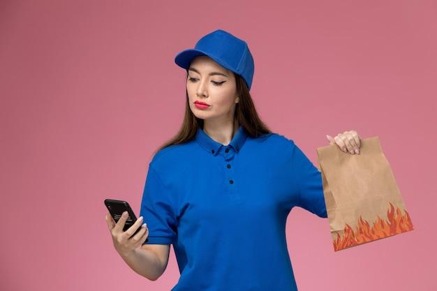 Vooraanzicht vrouwelijke koerier in blauw uniform en cape met een telefoon en voedselpakket op de roze muur