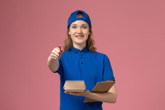 Vooraanzicht vrouwelijke koerier in blauw uniform en cape met kleine notitieblok voor bezorgvoedselpakket en schrijven op de roze muur, baan voor bezorgdienstmedewerker