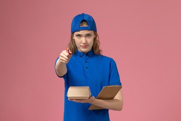 Vooraanzicht vrouwelijke koerier in blauw uniform en cape met kleine notitieblok voor bezorgvoedselpakket en schrijven op de roze muur, bezorgdienstmedewerker meisjesbaan