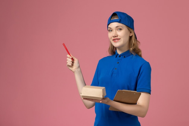 Vooraanzicht vrouwelijke koerier in blauw uniform en cape met kleine notitieblok voor bezorgvoedselpakket en schrijven op roze muur, medewerker van de baanbezorgdienst