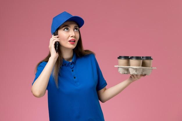 Vooraanzicht vrouwelijke koerier in blauw uniform en cape met koffiekopjes en smartphone op de roze muur