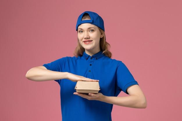 Vooraanzicht vrouwelijke koerier in blauw uniform en cape met weinig bezorgvoedselpakket op de roze achtergrond levering uniform dienst bedrijf werk werknemer baan