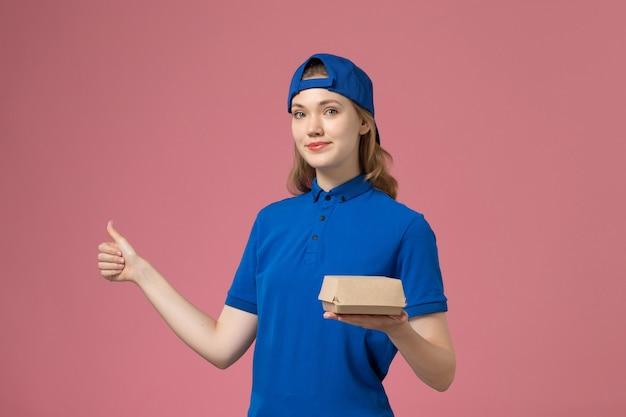Vooraanzicht vrouwelijke koerier in blauw uniform en cape met weinig bezorgvoedselpakket op de roze achtergrond levering uniform servicebedrijf werkbaan
