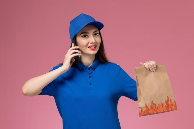 Vooraanzicht vrouwelijke koerier in blauw uniform en kaap pratende bedrijf voedselpakket op de roze muur