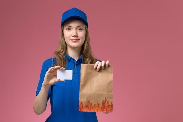 Vooraanzicht vrouwelijke koerier in blauw uniform glimlachend bedrijf witte kaart en voedselpakket op roze licht bureau dienst uniform bedrijf baan