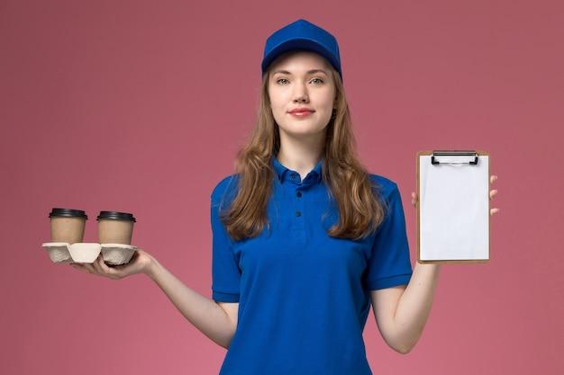Vooraanzicht vrouwelijke koerier in blauw uniform met bruine bezorgkoffiekopjes en blocnote op het roze uniform van de bureauservice die bedrijfsbaan levert