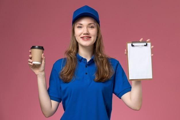 Vooraanzicht vrouwelijke koerier in blauw uniform met bruine koffiekopje met blocnote glimlachend op roze achtergrond service job uniform leverende bedrijf