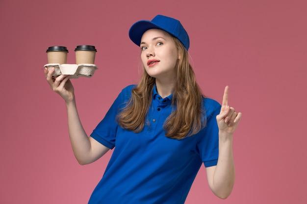 Vooraanzicht vrouwelijke koerier in blauw uniform met bruine levering koffiekopjes met opgeheven vinger op de roze achtergrond service uniform bedrijf baan bezorgen
