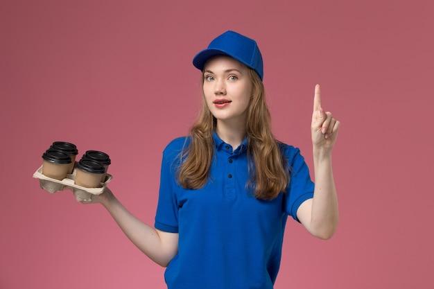 Vooraanzicht vrouwelijke koerier in blauw uniform met bruine levering koffiekopjes met opgeheven vinger op de roze desk service uniforme bedrijfsmedewerker